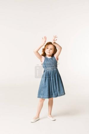 Little stylish child with arms up isolated on white