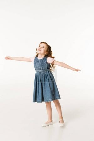 Little stylish kid in dress standing with wide arms isolated on white
