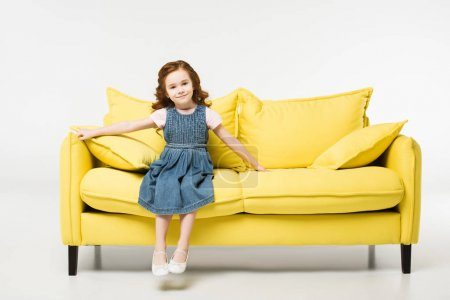 Photo for Stylish cute child in dress sitting on sofa isolated on white - Royalty Free Image