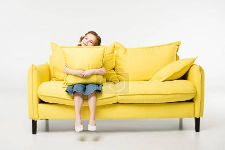 Photo for Little child with cushion in hands sitting on couch isolated on white - Royalty Free Image