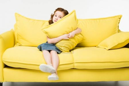 Little cute child embracing cushion while sitting on sofa isolated on white