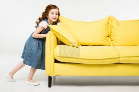 Stylish little kid in dress pushing sofa isolated on white