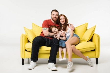 Photo for Happy family sitting on couch isolated on white - Royalty Free Image