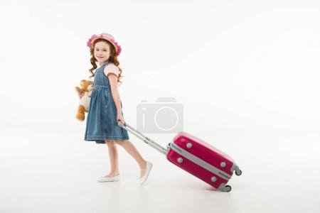 Little stylish child with teddy bear and suitcase isolated on white, travel concept