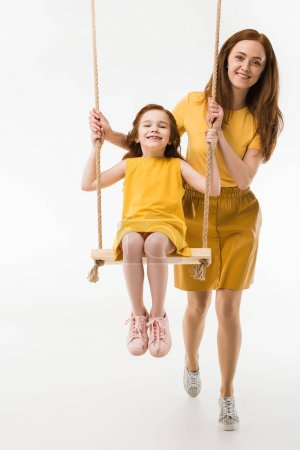 Mother riding happy little daughter on swing isolated on white