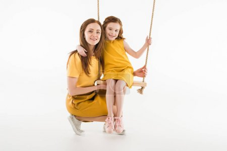 Smiling mother and daughter on swing isolated on white