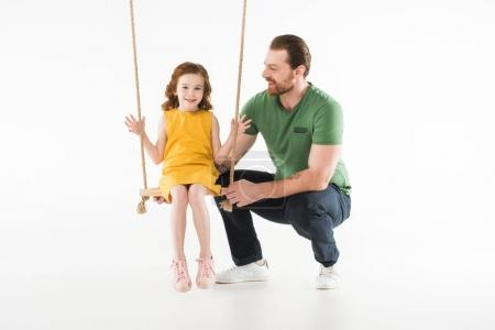 Father with happy daughter on swing isolated on white
