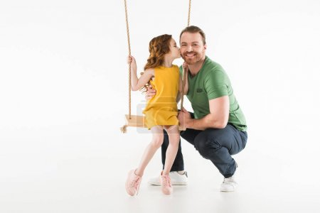 Little kid sitting on swing and kissing father isolated on white