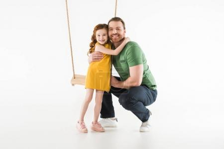 Daughter standing near swing and hugging father isolated on white