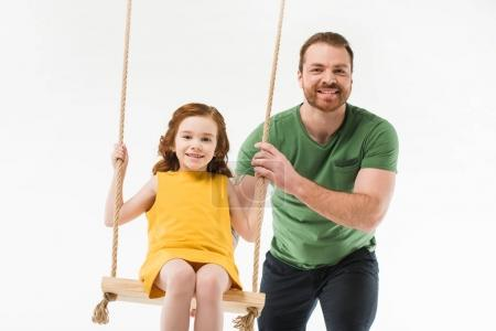 Smiling father riding little daughter on swing isolated on white