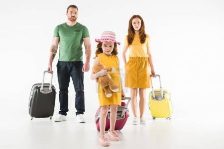 Photo for Upset little child with teddy bear and parents standing behind with suitcases isolated on white, travel concept - Royalty Free Image