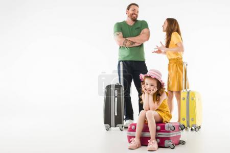 Photo pour Colère petit enfant assis sur la valise avec les parents derrière isolé sur blanc, le concept de voyage - image libre de droit