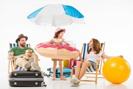 Happy little kid standing with flotation ring between parents sitting on sun loungers isolated on white, travel concept