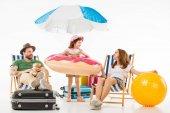 Niño feliz con un anillo de flotación entre los padres sentados en tumbonas de sol aislados en blanco, el concepto de viaje