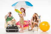 Family of tourists with sun loungers, sunshade, flotation ring and water gun isolated on white