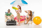 Parents sitting on sun loungers while daughter holding water gun isolated on white, travel concept