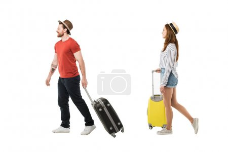 Stylish couple of tourists in hats carrying suitcases isolated on white, travel concept