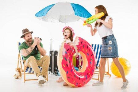 Foto de Padre teniendo tiro de cámara mientras la pistola de agua con el objetivo de madre a hija con el anillo de flotación aislado en blanco - Imagen libre de derechos