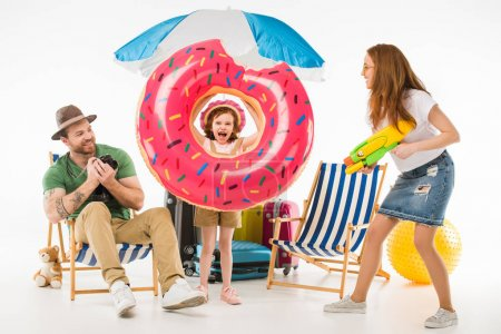 Family of tourists with flotation ring, camera and water gun isolated on white, travel concept