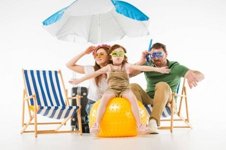 Family in swimming goggles with sunshade, sun loungers and ball isolated on white