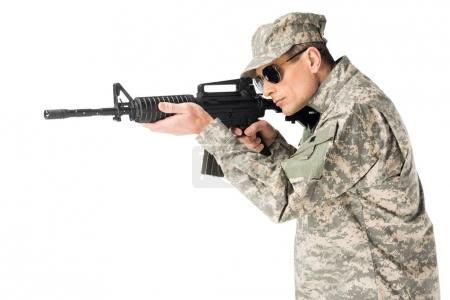 Soldier wearing uniform aiming with gun isolated on white