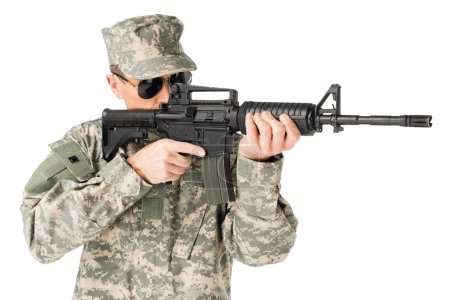Handsome army soldier wearing uniform aiming with gun isolated on white
