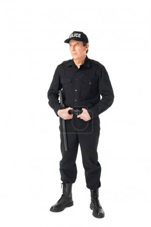 Confident policeman in uniform holding belt isolated on white