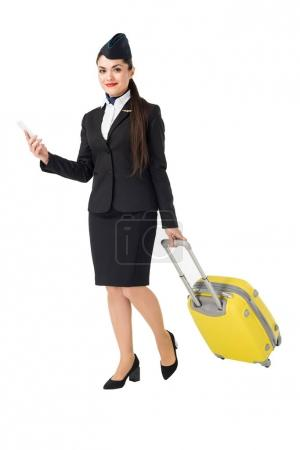 Young stewardess with suitcase using smartphone isolated on white