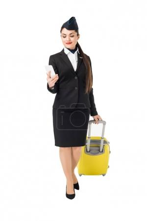 Young stewardess with suitcase looking at smartphone isolated on white