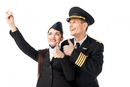 Photo for Smiling stewardess and pilot taking selfie isolated on white - Royalty Free Image