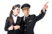 Pilot pointing showing stewardess something isolated on white