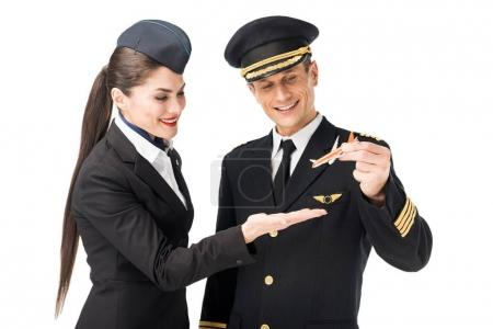 Airline captain and stewardess holding toy plane isolated on white