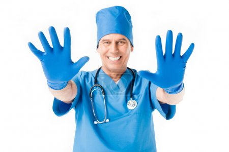 Smiling doctor showing hands in latex gloves isolated on white