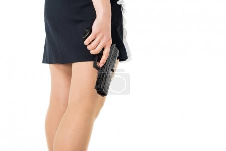 Close-up view of maid in uniform holding gun isolated on white