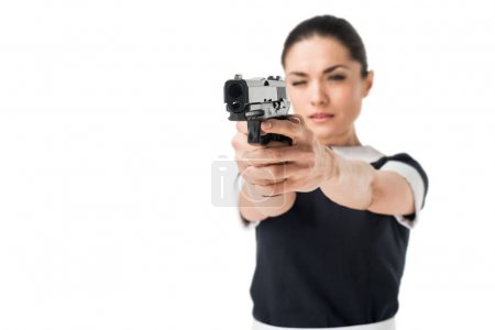 Young woman in maid uniform aiming gun isolated on white