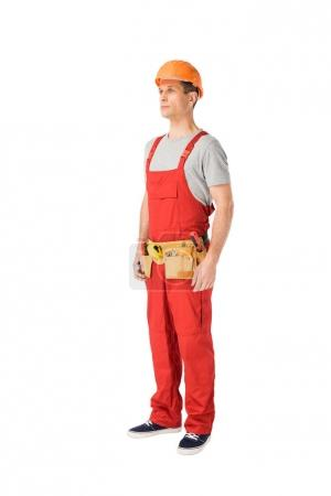 Handsome builder in uniform with tool belt isolated on white