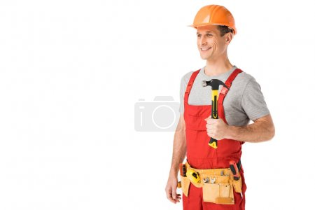 Smiling handyman in overalls holding hammer isolated on white