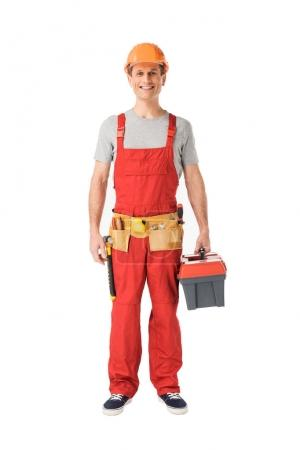 Smiling handyman in overalls holding toolbox isolated on white