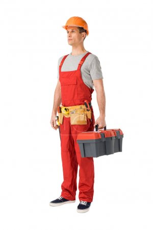 Handsome builder in uniform with tool belt holding toolbox isolated on white