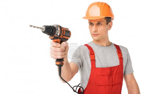 Professional builder in overalls and hardhat holding drill isolated on white