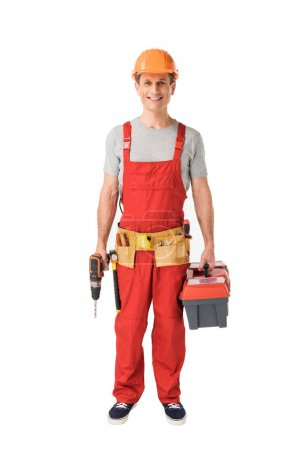 Cheerful construction worker in uniform holding toolbox and drill isolated on white