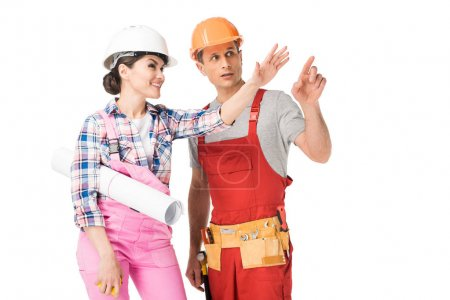 Professional builders man and woman holding blueprint and ruler isolated on white