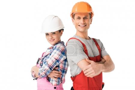 Male and female builders in hardhats and overalls isolated on white