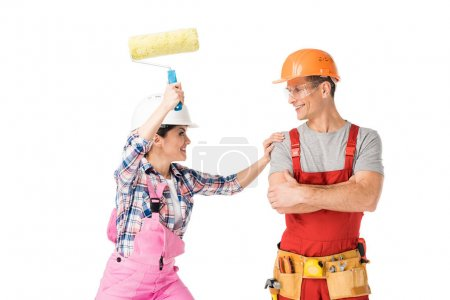 Male and female builders fooling around with paint roller isolated on white