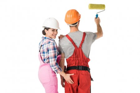 Woman in builder uniform touching buttocks of man with paint roller isolated on white