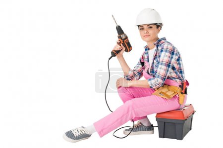 Professional builder in overalls and hardhat holding drill while sitting on toolbox isolated on white
