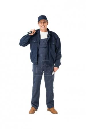 Handsome plumber in overalls holding adjustable wrenches isolated on white
