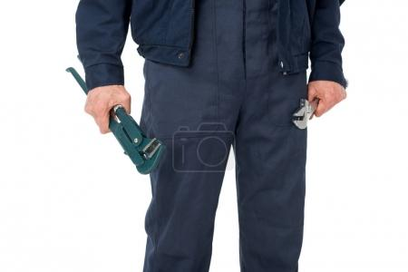 Close-up view of plumber  holding adjustable wrenches isolated on white