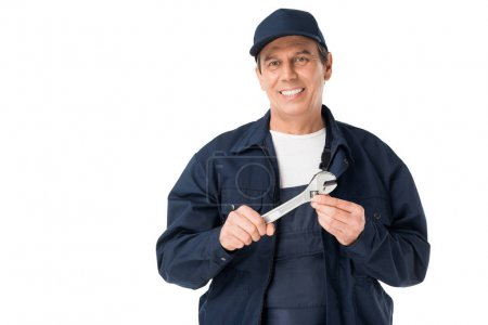 Smiling repairman holding adjustable wrench isolated on white