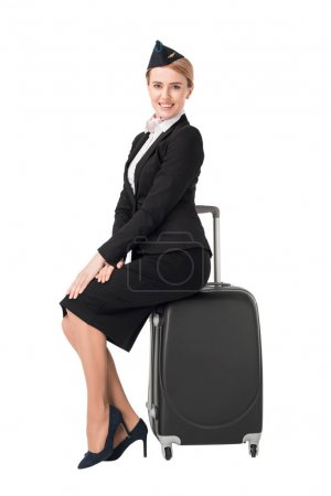 Young female stewardess sitting on suitcase isolated on white